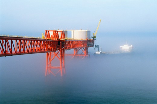 Tanker filling up from offshore drilling facility : Stock Photo