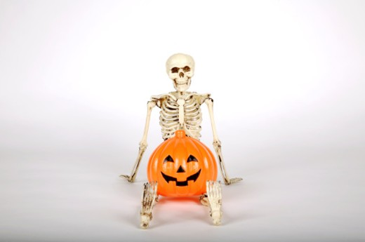 Skeleton Model Sitting with Pumpkin : Stock Photo