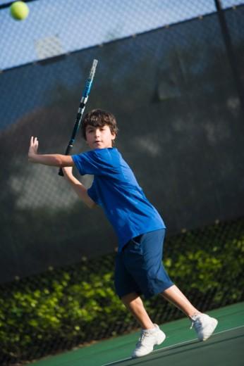 Stock Photo: 1598R-9991288 Boy (9-10) playing tennis, Miramar, Florida, USA