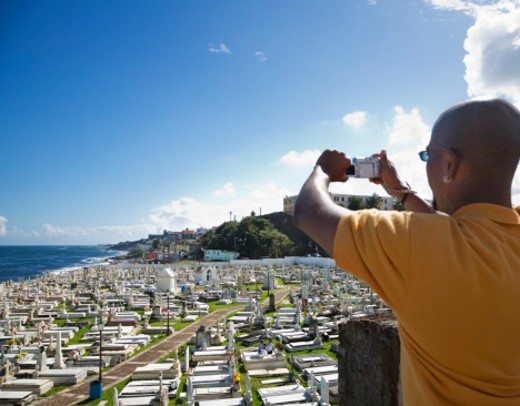 Tourist taking photo of cemetery with digital camera in Old San Juan, Puerto Rico : Stock Photo