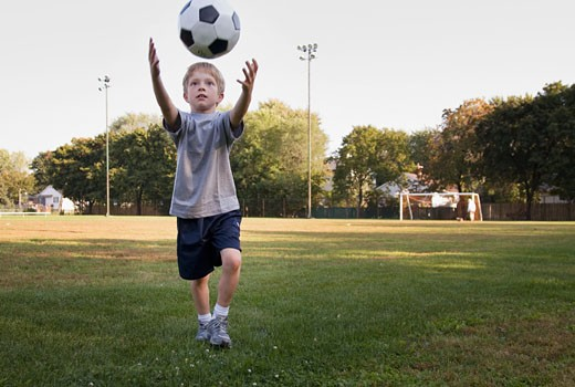 Young boy playing with soccer ball in field behind school : Stock Photo