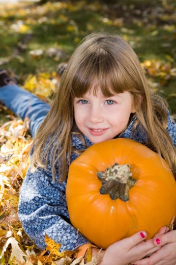 Stock Photo: 1598R-9993306 A beautiful 6 year old girl holding her pumpkin on a fall day.