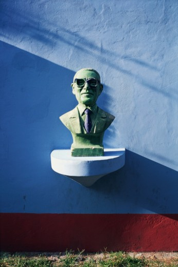 Stock Photo: 1598R-9993420 Bust of man wearing glasses and a business suit resting on ledge along street in Buenos Aires, Argentina