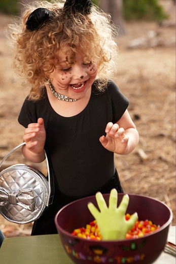 Little girl in cat costume with candy bowl. : Stock Photo