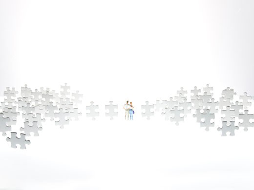a couple stands in the pieces of puzzles : Stock Photo