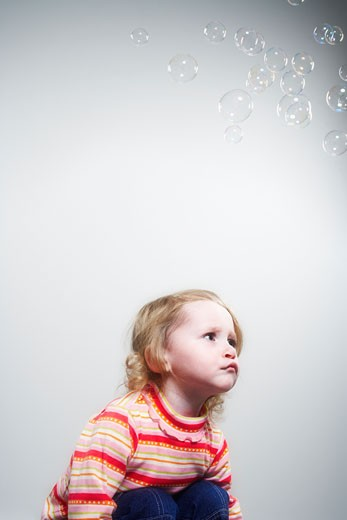 Stock Photo: 1598R-9993839 Toddler sitting with bubbles floating overhead