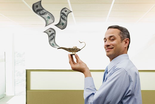 Business man in office with magic lantern spewing out dollars  : Stock Photo