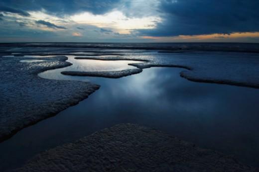 Stock Photo: 1598R-9996419 The sun sets over an estuary on the Norfolk coast line.