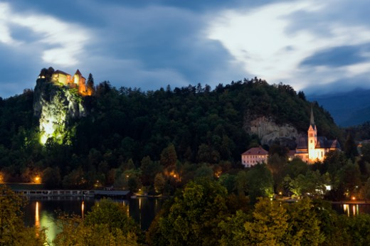 Stock Photo: 1598R-9997258 View of the main town of Bled with local church and shops. Bled Castle on cliffside is also featured with lights.  Lake Bled, Slovenia at dusk