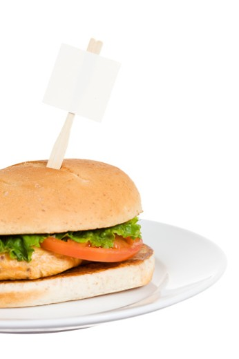 Fast food chicken sandwich with blank sign.  Various food items in this series, with a small sign sticking out, suitable for adding text to.  Also, most have accompanying images without signage. : Stock Photo