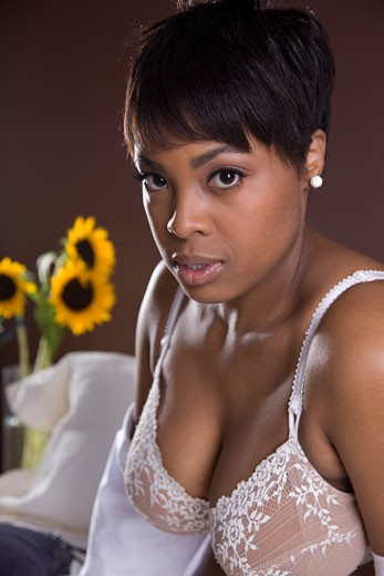 Beautiful black woman looks seductively at the camera in the bedroom. : Stock Photo
