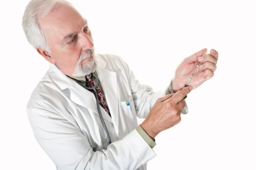Doctor preparing a shot to give to patient : Stock Photo