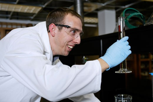 Stock Photo: 1598R-9998201 Chemist smiling while checking his experiment. He is holding a glass cylinder in a lab setting.
