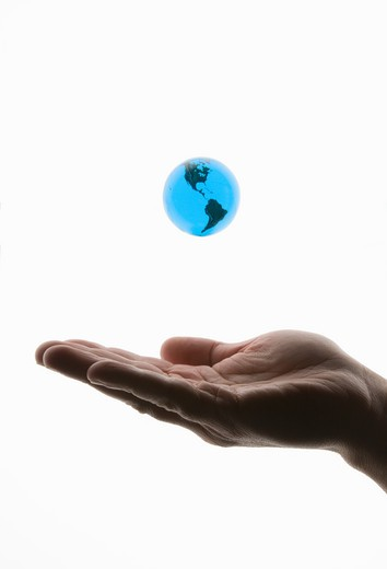 Small world globe floating over a man's hand on a white background. : Stock Photo