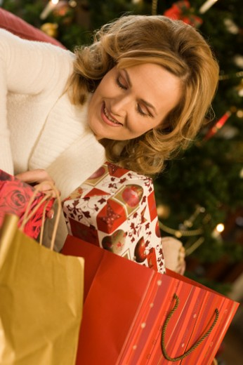 woman with bags full of christmas gifts, christmas tree in the background : Stock Photo