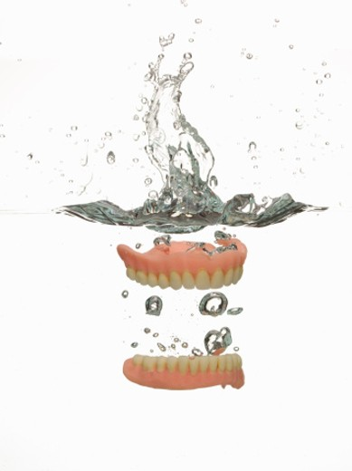 Dentures in water : Stock Photo