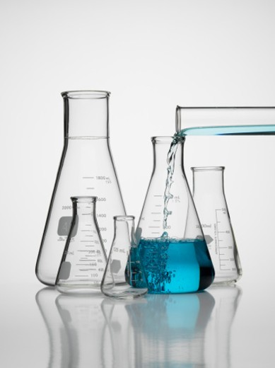 Scientific glassware and pour : Stock Photo