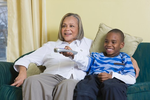 Young African American boy playing with the remote with his Grandmother : Stock Photo