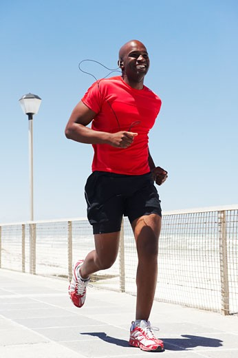Stock Photo: 1598R-9999772 black male with headphones running on beach promenade by coloured beach huts wearing a red t shirt