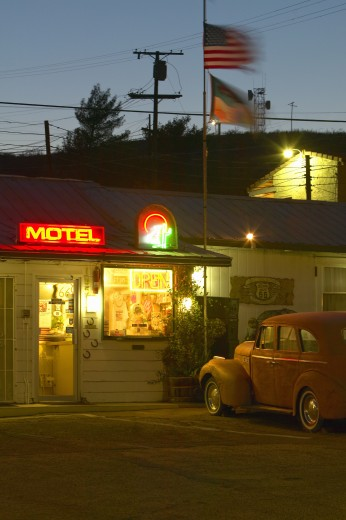 Route 66 neon sign and historic vintage roadside motel welcomes old cars and guests in Barstow California : Stock Photo