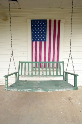 Old swing on porch displaying an American Flag and patriotic theme near Barstow CA off Route 59 : Stock Photo