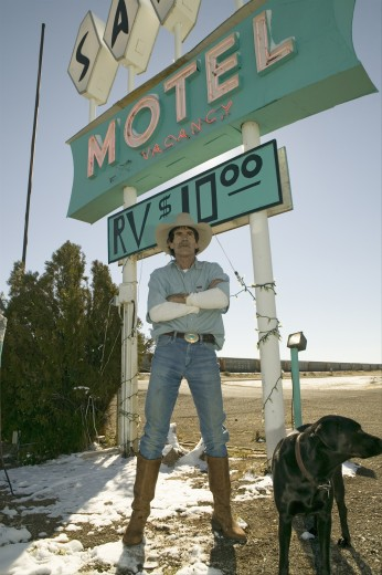 Stock Photo: 1599-11941 Cowboy with dog stand in front of Sands Motel sign with RV Parking for $10, located at the intersection of Route 54 & 380 in Carrizozo, New Mexico
