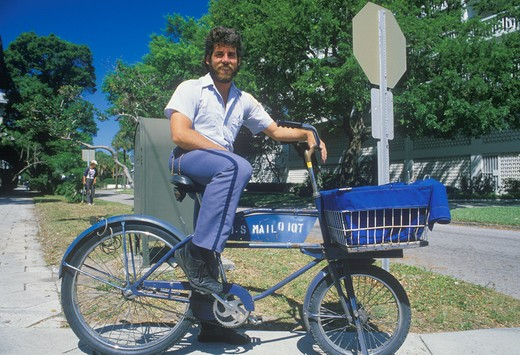 An Latino mail carrier bicycling on his route, St. Petersburg, FL : Stock Photo
