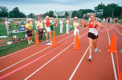 Stock Photo: 1599-12484 A female runner crossing the finish line at the Senior Olympics, St. Louis, MO
