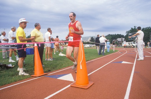 Runner crosses the finishing line at the Senior Olympics, St. Louis, MO : Stock Photo