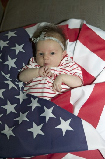 Stock Photo: 1599-12781 Newborn baby (Sophia Larson) wrapped in American flag was born on October 16th, the birthday of the 300 Millionth American, Ventura, California
