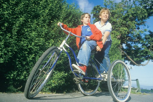Two boys riding a three wheeled bicycle, Ferndale, CA : Stock Photo