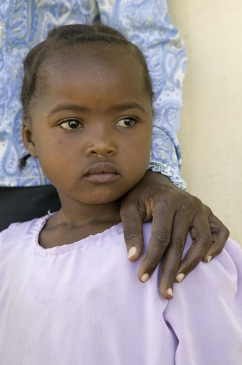 A young Kenya girl, infected with HIV/AIDS, stands beside Khadija Rama, founder of Pepo La Tumaini Jangwani, HIV/AIDS Community Rehabilitation Program, Orphanage & Clinic.  Pepo La Tumaini Jangwani (wind of hope in the arid place) offers hope, support and care for orphan and vulnerable children living with HIV/AIDS in Nairobi, Kenya, Africa : Stock Photo
