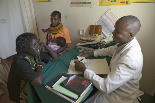A doctor consults with mother and children about HIV/AIDS at Pepo La Tumaini Jangwani, HIV/AIDS Community Rehabilitation Program, Orphanage & Clinic.  Pepo La Tumaini Jangwani (wind of hope in the arid place) offers hope, support and care for orphan and vulnerable children living with HIV/AIDS in Nairobi, Kenya, Africa : Stock Photo