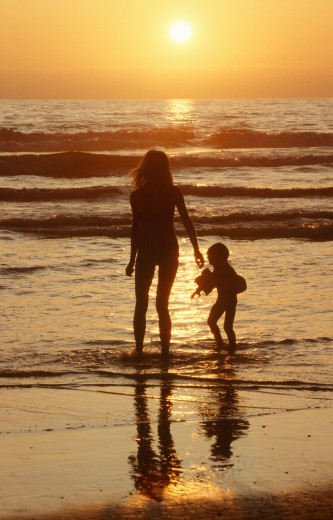 Silhouetted girl and child walking on beach at sunset, San Diego, California : Stock Photo