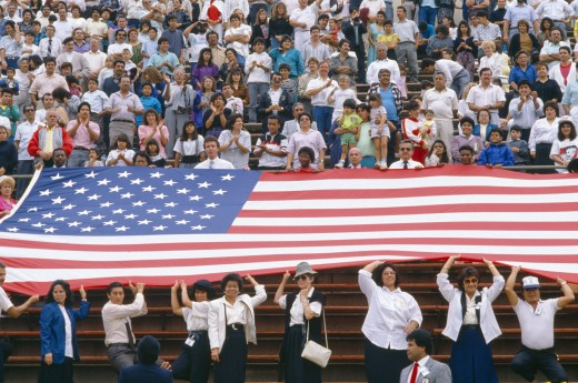 Crowd at sports event with large American flag : Stock Photo