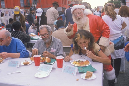 Santa Claus posing with the homeless for Christmas dinner, Los Angeles, California : Stock Photo