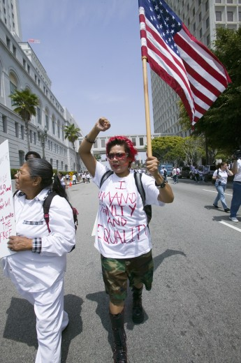 Stock Photo: 1599-4675 Protestor carries US flag demanding equality with hundreds of thousands of immigrants participating in march for Immigrants and Mexicans protesting against Illegal Immigration reform by U.S. Congress, Los Angeles, CA, May 1, 2006