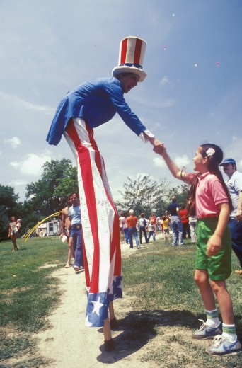 Man on Stilts Dressed As Uncle Sam Shaking Girl's Hand, Salina, Kansas : Stock Photo