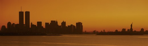 This is the Manhattan skyline from New Jersey. It shows the Statue of Liberty on the right, the world Trade Towers on the left and the skyline in silhouette at sunrise. : Stock Photo