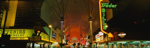 This is part of the strip in Las Vegas known as the Fremont Street Experience. There are neon lights lighting up the strip from the casinos at night. : Stock Photo