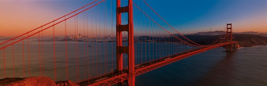 Stock Photo: 1599-6703 This is the Golden Gate Bridge at sunset. It is the view from the Marin Headlands. The skyline is small in the distance.
