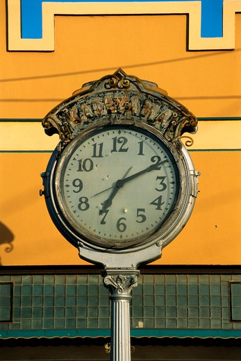 Stock Photo: 1599-6999 This is a vintage clock in morning light. The time on the clock is 7:11. It has a white face and black hands with silver ornate trim.
