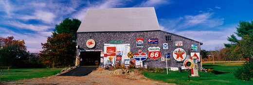 This is a New England barn with numerous signs posted on the outside of it. The signs are old advertising signs from various oil companies, as well as Marlboro. There are as a couple of vintage gas pumps from old gas stations. The owner is a collector of old signs and junk. It is a roadside attraction and piece of Americana. : Stock Photo