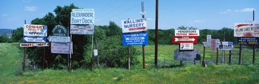 These are road signs found in the hill country in central Texas.  The signs advertise various services and point the way to find them. The time of year is spring.  There are green trees behind them and green grass below them. : Stock Photo