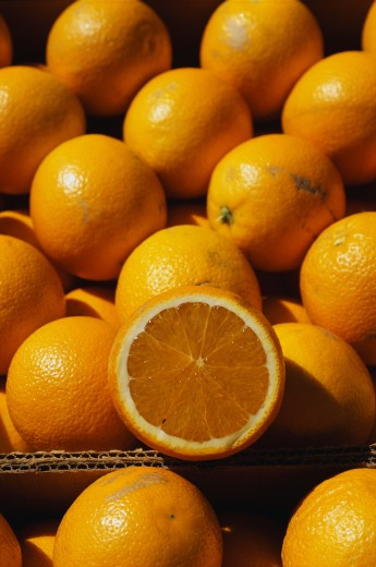 This is a close up of a boxes of oranges. One of the oranges has been sliced in half. : Stock Photo