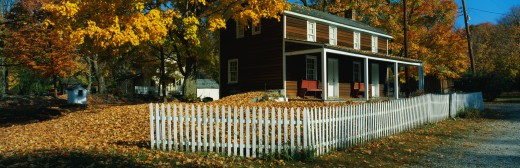 This is a brown, wooden house in a historic village near the Delaware River. A white picket fence surrounds the house. There are autumn leaves on the trees surrounding the property. : Stock Photo