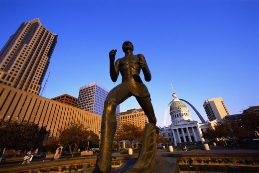 This is the Old Courthouse with a close up of the statue in front of the courthouse and State Capitol. In the background is the skyline and arch. : Stock Photo