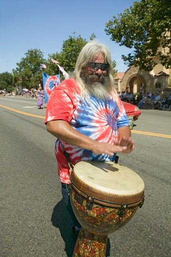 Hippie in red, white and blue tie-dye t-shirt pounds his drum down main street during a Fourth of July parade in Ojai, CA : Stock Photo