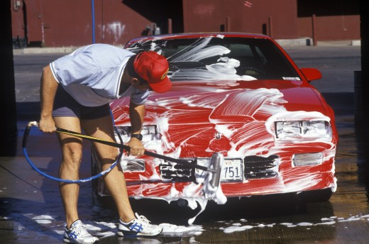 A man washing his red car in Barstow, California : Stock Photo