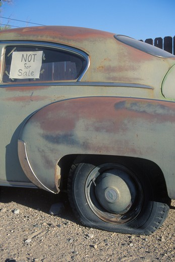 Stock Photo: 1599-8239 An old car with a flat tire has a not for sale sign in its window
